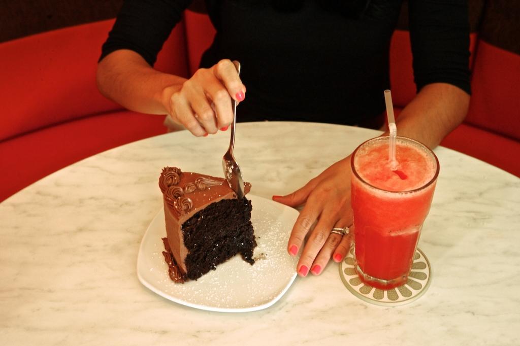 Woman eating a chocolate cake.